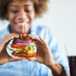 woman eating burger from Kingstowne's Irish pubs