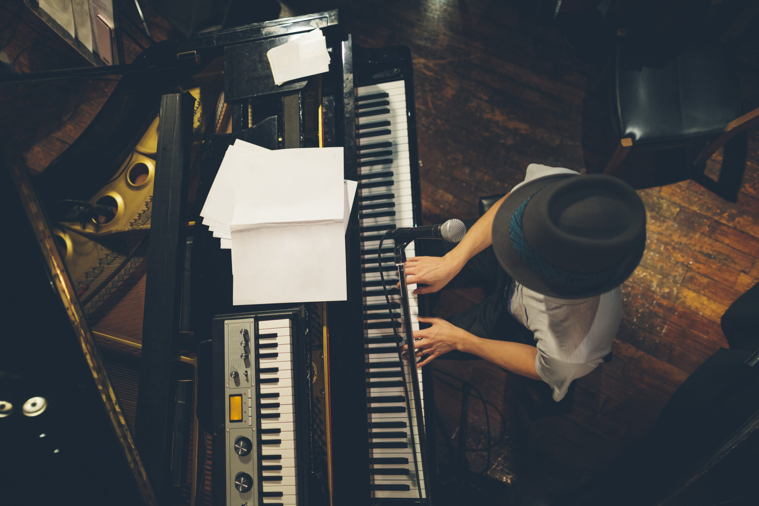 Overhead photo of man with fedora hat sitting at piano keyboard with music sheets on top for Kennedy Center performances