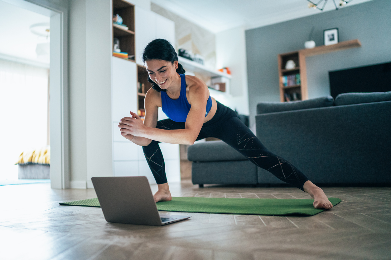 woman in front of laptop on exercise mat taking Fairfax County Library Virtual Activities