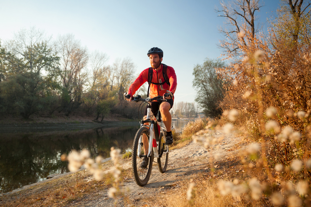 man biking on a trail with gear from bicycle shops near Kingstowne